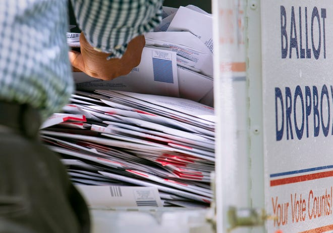 An elections office worker empties ballots from a dropbox outside the Palm Beach County Supervisor of Elections main office in West Palm Beach on Oct. 5 as voters flocked to the site to cast their vote-by-mail ballots. LANNIS WATERS/THE PALM BEACH POST