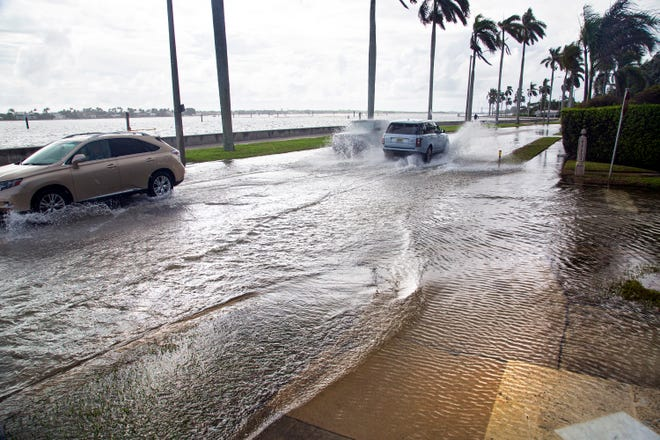 Water from the Intracoastal Waterway floods Greenwood Drive at South Flagler Drive in West Palm Beach at high tide on Oct. 18.