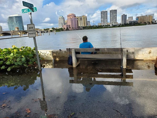 King tide flooding did not deter fisherman, who took over benches and stood atop the low wall along the western side of Lake Trail in Palm Beach on Sunday, Oct. 18, 2020.