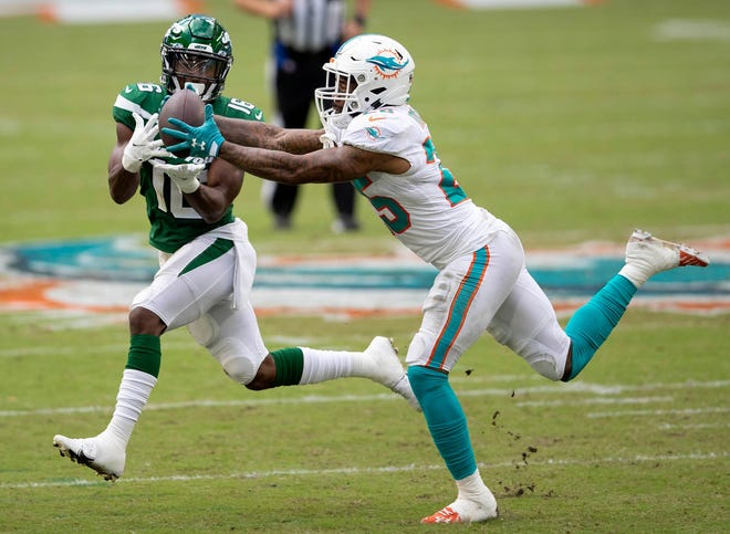 Cornerback Xavien Howard intercepts a pass intended for Jets receiver Jeff Smith in the second quarter Sunday at Hard Rock Stadium.