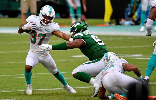 Miami Dolphins running back Myles Gaskin (37) stiff arms New York Jets defensive end John Franklin-Myers (91) during the first half at Hard Rock Stadium.