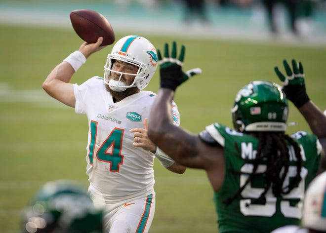 Dolphins quarterback Ryan Fitzpatrick throws a touchdown to tight end Durham Smythe as Jets nose tackle Steve McLendon applies pressures Sunday at Hard Rock Stadium in Miami Gardens.