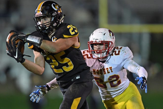 Garfield's Anthony Demma catches a pass before being hit by Mooney's AJ Pecchia during the second half of Saturday night's OHSAA playoff game. Garfield won 24-21.