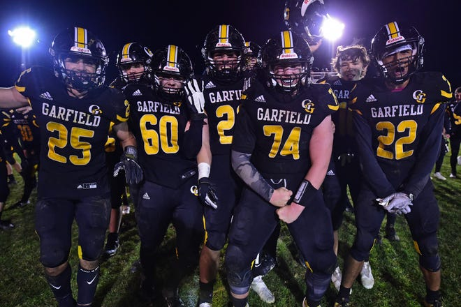 Garfield's Anthony Demma (25), Shawn Barber (60), Noah Eggert (23), Riley LaPorte (74) and Joe Perrine (22) celebrate after Garfield defeated Cardinal Mooney 24-21 in their OHSAA playoff game Saturday night.