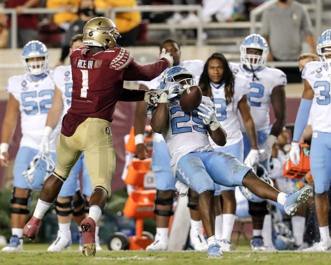 Runningback Javonte Williams (25) of the North Carolina Tar Heels makes a catch over Linebacker Emmett Rice  of the Florida State Seminoles during the game at Doak Campbell Stadium on Bobby Bowden Field on October 17, 2020 in Tallahassee, Florida. Florida State upset No. 5 North Carolina 31 to 28. (Photo by Don Juan Moore/Character Lines)