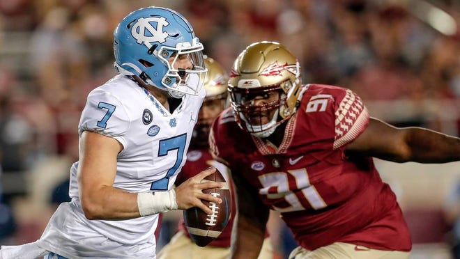 North Carolina quarterback Sam Howell is chased by Florida State defensive lineman Robert Cooper, right, during Saturday night's game.