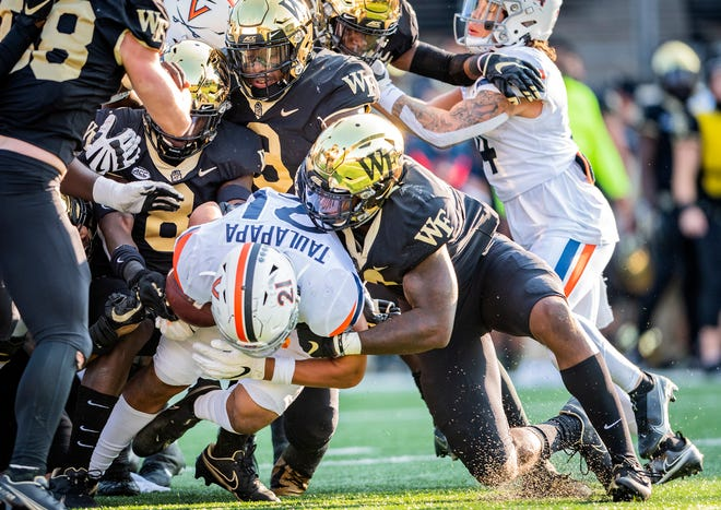 A gang of Wake Forest defenders tackle Virginia running back Wayne Taulapapa on Saturday.