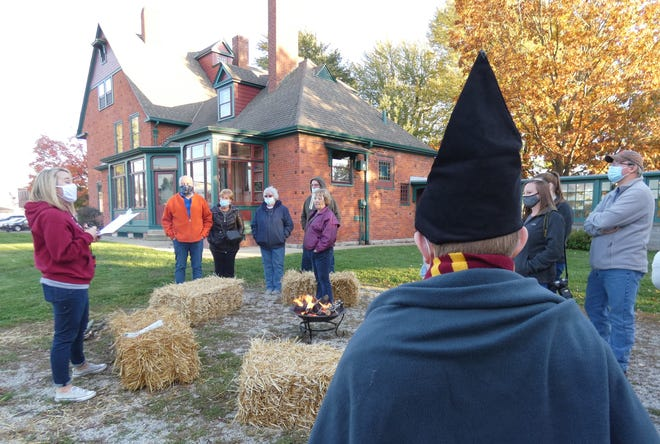 Tanesha Pickering, left, shares a little of the history of Brownella Cottage as a  ghost tour begins Friday.