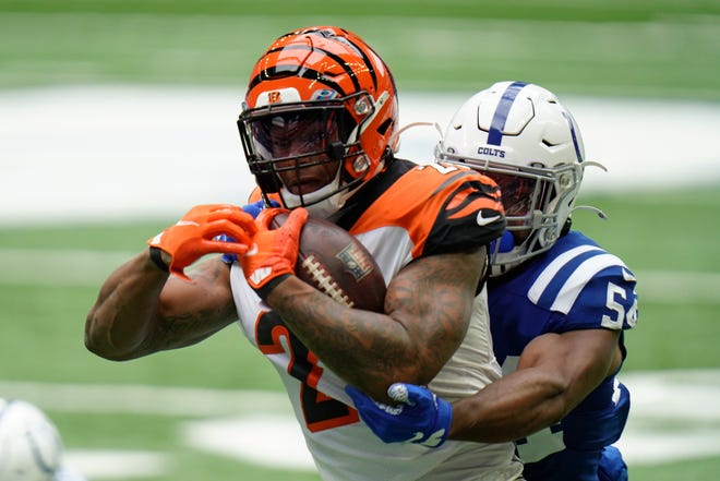 Cincinnati Bengals' Joe Mixon (28) is tackled by Indianapolis Colts' Anthony Walker (54) during the first half of an NFL football game, Sunday, Oct. 18, 2020, in Indianapolis.