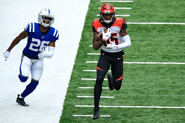 Tee Higgins #85 of the Cincinnati Bengals runs with a catch, pursued by Rock Ya-Sin #26 of the Indianapolis Colts during the first half at Lucas Oil Stadium on October 18, 2020 in Indianapolis, Indiana.