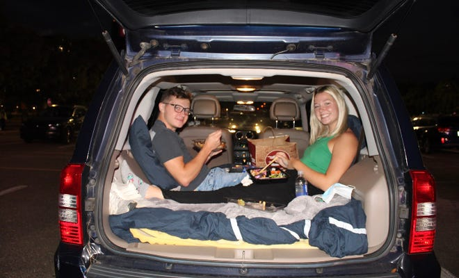 """Nick Bass and Gwen Alexander await the screening of """"The Nightmare Before Christmas"""" from the trunk of their car at the drive-in event."""