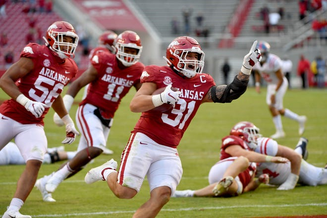 Arkansas defensive back Grant Morgan (31) celebrates as he returns an interception for a touchdown against Mississippi during the second half Saturday in Fayetteville.