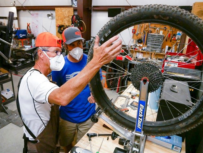 This Sept. 29, 2020, image shows volunteer Jan Bear, left, and shop owner Charlie O'Leary inspecting a mountain bike wheel at O'Leary Built Bicycles in Santa Fe, New Mexico. With limited access to gyms, people are snatching up bikes as soon as they hit the sales floor. In Santa Fe, retailers are struggling to keep bikes in stock.