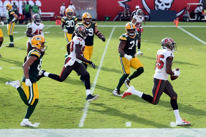Tampa Bay Buccaneers cornerback Jamel Dean (35, right) heads for the endzone after intercepting a pass by Green Bay Packers quarterback Aaron Rodgers and returning it for a score during the first half of an NFL football game Sunday, Oct. 18, 2020, in Tampa, Fla.
