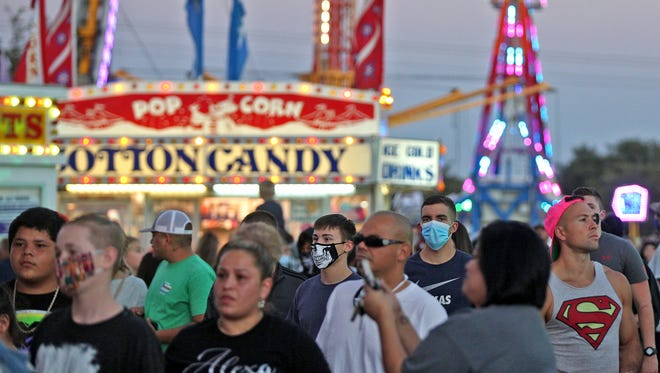 People line up for a ride during a carnival at the Sunset Mall on Saturday, Oct. 17, 2020.