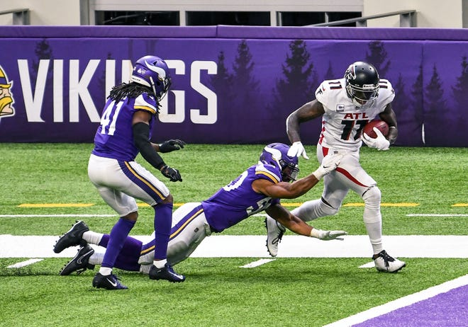 Atlanta Falcons wide receiver Julio Jones (11) breaks the tackle attempt of Minnesota Vikings linebacker Eric Wilson (50) on his way to the end zone for a 40-yard touchdown reception in the third quarter at U.S. Bank Stadium.