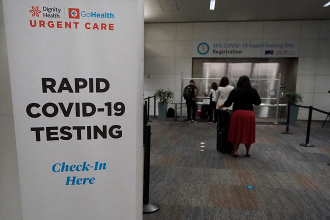 People wait in line to register for rapid COVID-19 testing at San Francisco International Airport on Thursday.