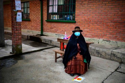An indigenous woman sits on a bench as she waits at a polling station in Huarina, Bolivia, on Oct. 18, 2020 during the country's general election. Landlocked Bolivia elects a new president on Sunday after a 2019 poll was annulled and follow-up elections postponed twice amid the COVID-19 novel coronavirus pandemic.