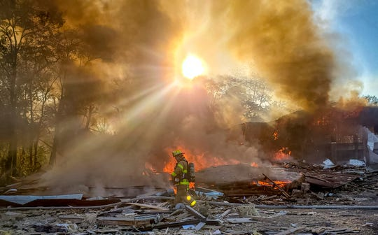 A firefighter passed through the burning remains of a shopping center after an explosion in Harrisonburg, Va., On October 17, 2020.