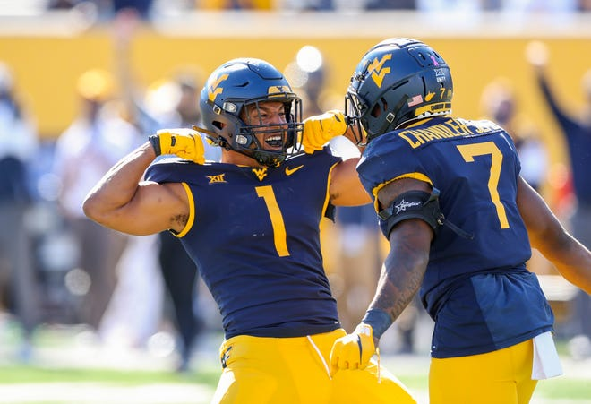 West Virginia Mountaineers linebackers Tony Fields II and Josh Chandler-Semedo (7) celebrate after a defensive stop during the third quarter against the Kansas Jayhawks on Saturday. Chandler-Semedo, a McKinley product, was named Big 12 Defensive Player of the Week on Monday.