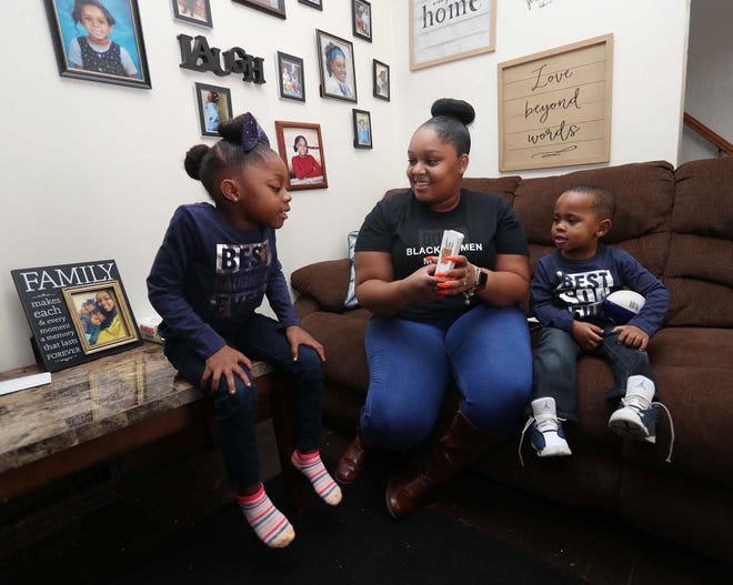 Jasmine Burgan listens as her daughter Madison, 5, spells out the image on the vocabulary cards she is using with her son Mason, 2, at their home in Akron.