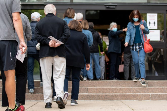 Voters wait in long lines to drop off their absentee and mail-in ballots at the Bucks County Administration Building in Doylestown Borough on Monday, October 19, 2020.