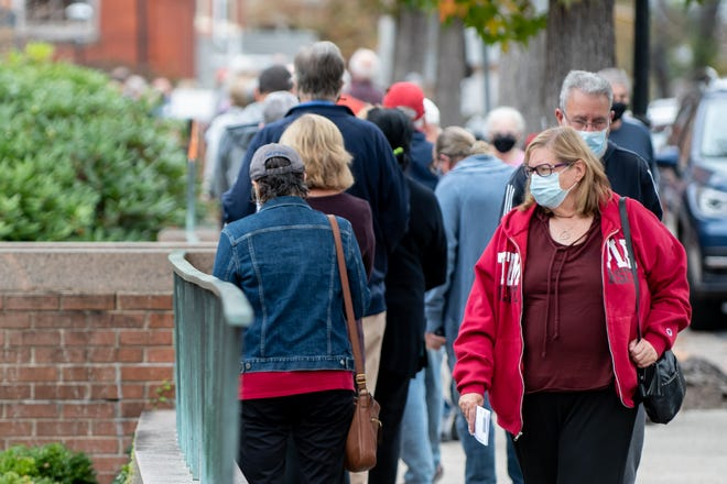 Voters make their way to the end of a long line to drop off their absentee and mail-in ballots at the Bucks County Administration Building in Doylestown Borough on Monday, October 19, 2020.