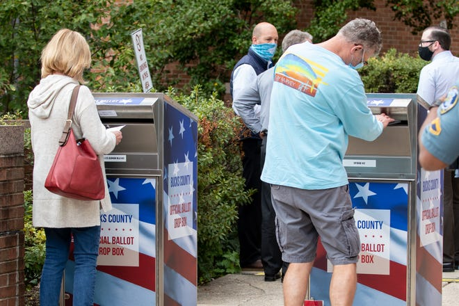 Voters insert their mail-in ballots into drop boxes outside the Bucks County Administration Building in Doylestown Borough on Monday, October 19, 2020.