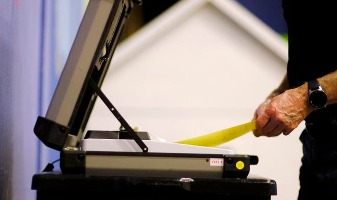 A voter feeds his ballot in the voting machine while voting at Precinct 61 in Edmond on Tuesday, August 25, 2020.