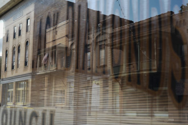 Buildings along Main Street are reflected in the front window of the Little Cities of Black Diamonds Council office on Friday, Sept. 18, 2020 in Shawnee, Ohio. The town, in Appalachian Perry County, was once a bustling coal mining town. Now, local residents are revitalizing the once-beautiful and long-forgotten coal mining town. The LCBD Council is a non-profit organization run by Cheryl Blosser dedicated to the history and lives of former coal mining towns throughout Athens and Perry counties.