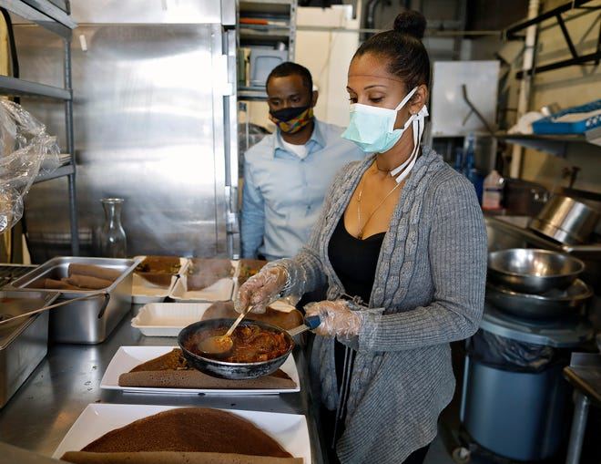 Tigi Zemene, front, and Birhan Ayele prepare mushroom combos to serve at the new Nile Vegan in Grandview Heights. [Kyle Robertson/Dispatch]