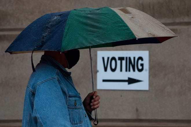 A voter waits in line during early voting last week at the Franklin County Board of Elections Early Voting Center in Columbus. Despite steady rain all morning, voters waited for up to 45 minutes to cast their ballot.