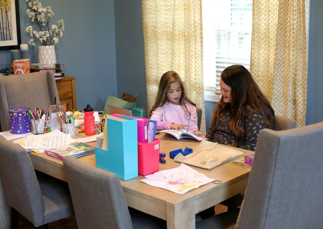 Audrey Saurer, 7, reads to her mom, Lisa Saurer, in their Gahanna home where she does schoolwork. Audrey is thrilled that she soon will be able to attend classes at High Point Elementary School, now that a teachers strike is over.