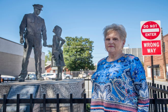 Carolyn Everhart, who retired after 40 years as the parking enforcement officer for the Lexington Police Department, stands in front of the police statue at the department.