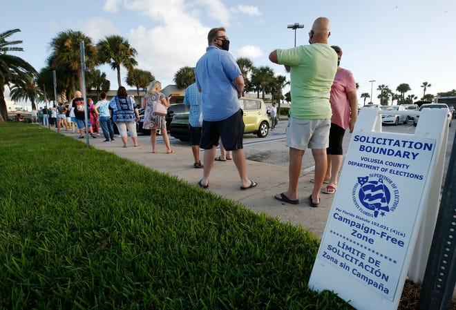 Voters line up City Island in Daytona Beach to cast their vote as early voting begins, Monday, Oct. 19, 2020.