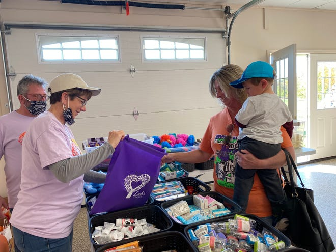 Robin and Susan Cox of Allentown helped Katha Baer of Mercersburg, with grandson Lawson Leasure, 3, fill a Leah's Legacy bag with items for women in recovery homes and support groups.
