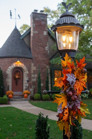 Colorful fall decor surrounds this brick home.