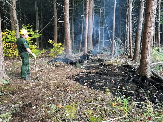 A Forest Ranger monitors a small ground fire at Ossian State Forest.