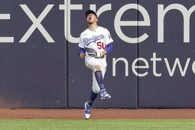 Los Angeles Dodgers right fielder Mookie Betts celebrates after robbing the Atlanta Braves' Marcell Ozuna of a home during Game 6 of the National League Championship Series Saturday in Arlington, Texas.
