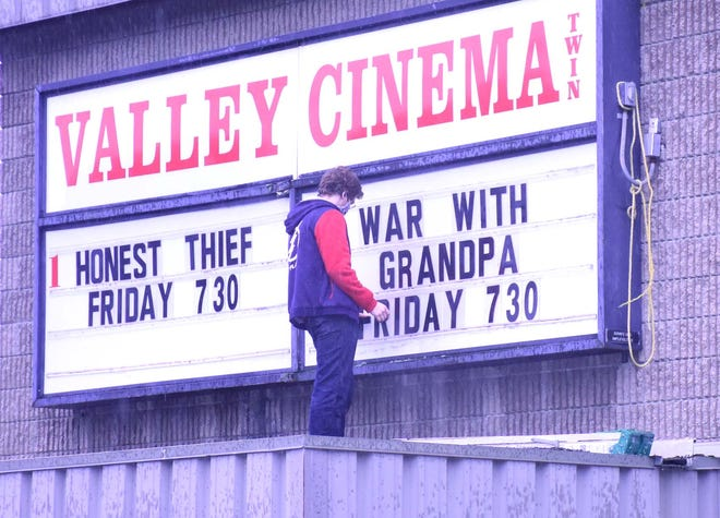 Theater manager Devan Durkee checks the positioning of his letters after updating the marquee at Valley Cinemas in Little Falls, New York, last week. The theater had planned to reopen Friday following Gov. Andrew Cuomo's announcement that some New York theaters can reopen for the first time since the coronavirus pandemic closed them in March, but had to delay the opening until Saturday while some technical issues were resolved.