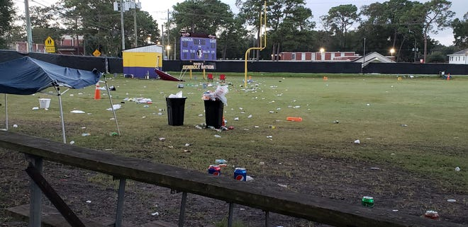 Soda cans and food containers litter the Arlington Football Association field a day after a man was shot dead and his 7-year-old son wounded while watching a youth game there Sunday.
