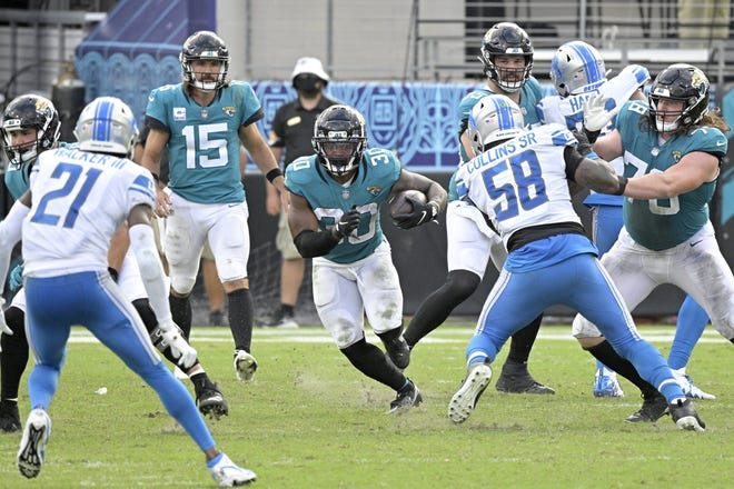 This was a rare instance when Jaguars running back James Robinson (30) had a little bit of room to run in-between the tackles. The Detroit Lions held him to 29 yards rushing  in a 34-16 win over the Jaguars. (AP Photo/Phelan M. Ebenhack)