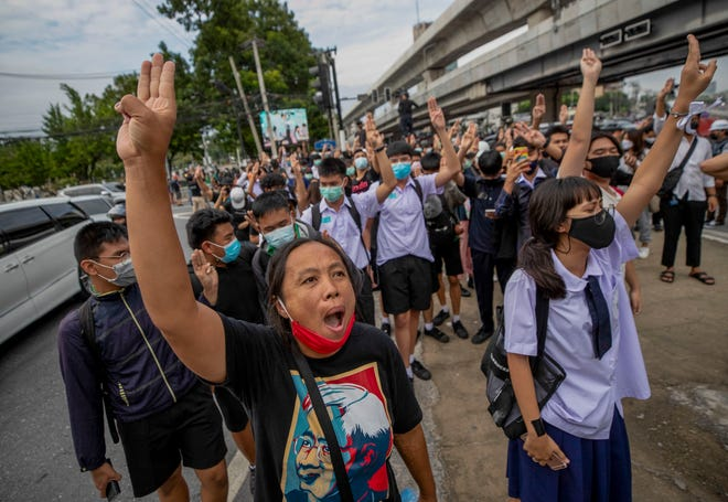 Pro-democracy protesters flash three-fingered salute during a demonstration at Kaset intersection, suburbs of Bangkok, Thailand, on Monday. Thailand's embattled Prime Minister Prayuth Chan-ocha said Monday that there were no plans to extend a state of emergency outside the capital, even as student-led protests calling for him to leave office spread around the country.
