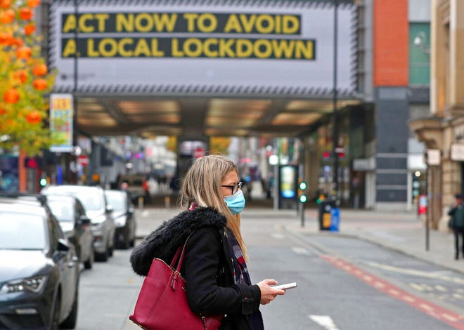 A woman wearing a face mask walks in Manchester, England, Monday, Oct. 19, 2020. Britain's government says discussions about implementing stricter restrictions in Greater Manchester must be completed Monday because the public health threat caused by rising COVID-19 infections is serious and getting worse.