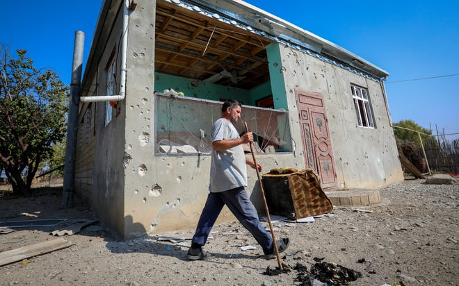 A man walks past a house damaged by shelling during fighting over the breakaway region of Nagorno-Karabakh in Agdam, Azerbaijan, on Monday. Reports of renewed shelling on Monday challenged the new cease-fire in the conflict over the separatist territory of Nagorno-Karabakh, where heavy fighting between Armenian and Azerbaijani forces has raged for over three weeks.