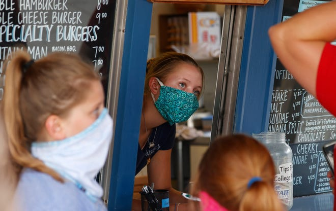 A staffer wears a mask while taking orders in August at a small restaurant in Grand Lake, Colo., amid the coronavirus pandemic. The coronavirus pandemic has put millions of Americans out of work. But many of those still working are fearful, distressed and stretched thin, according to a new poll by The Associated Press-NORC Center for Public Affairs Research.