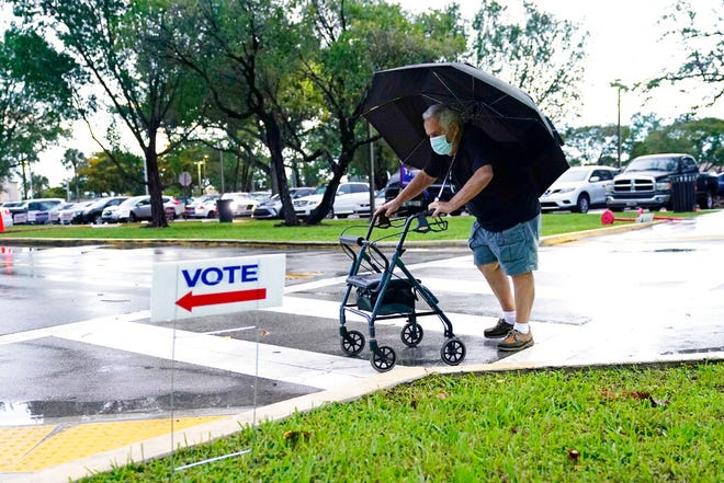 Franklin Castellon, 76, shields himself from the rain as he walks to an early voting site, Monday, Oct.19, 2020, in Miami. Florida begins in-person early voting Monday in much of the state as the Trump campaign tries to cut into an early advantage Democrats have posted in mail-in votes in the key swing state.