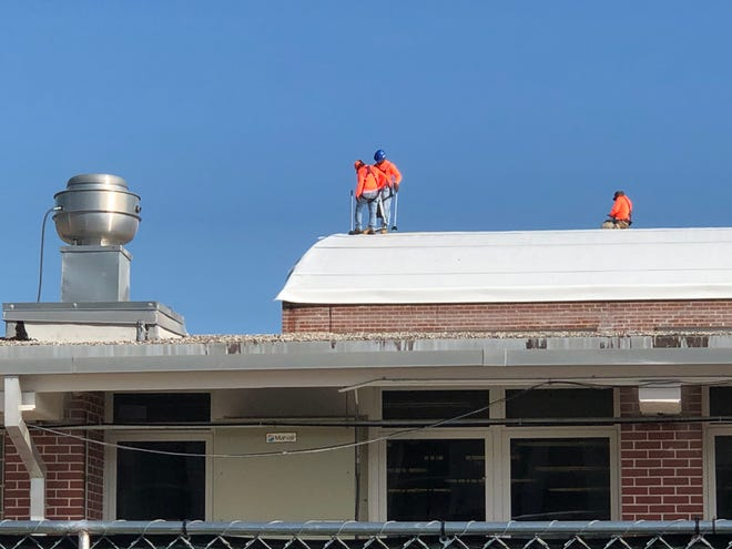 Construction workers work atop the gym at Kathleen Middle School on Monday. Several buildings at the school were severely damaged by an EF-2 tornado the night of Oct. 18, 2019.