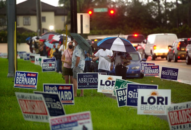 People brave rainy weather as they line up to vote at the Lantana Road Branch Library during the first day of in-person early voting in Palm Beach County on October 19, 2020 in Lake Worth.