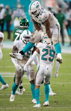 Miami Dolphins defensive tackle Christian Wilkins (94) leaps over Miami Dolphins free safety Brandon Jones (29) after Jones stopped New York Jets running back Frank Gore (21) behind the line of scrimmage at Hard Rock Stadium in Miami Gardens, October 18, 2020.  [ALLEN EYESTONE/The Palm Beach Post]